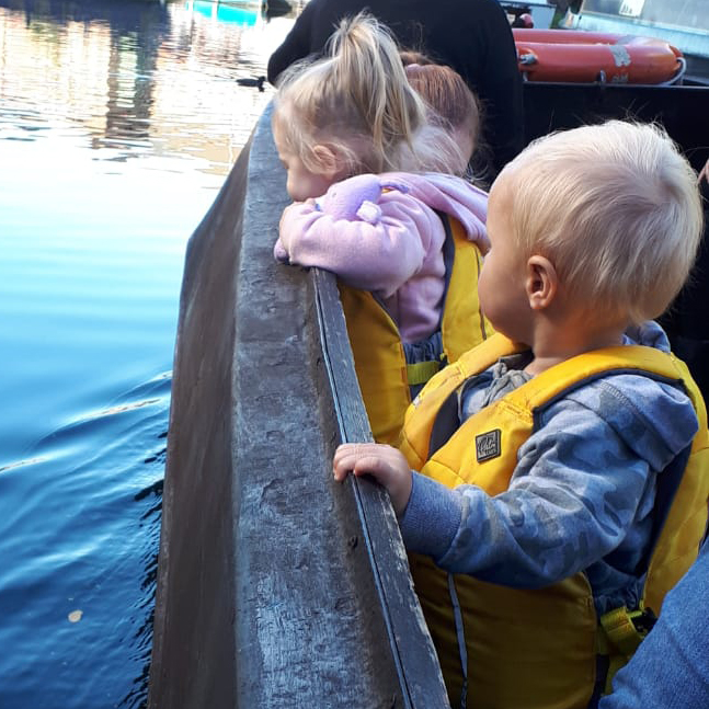 Three small children wearing lifejackets stand at the side of a narrow boat looking over the edge at the water. Their heads are turned away from the camera.