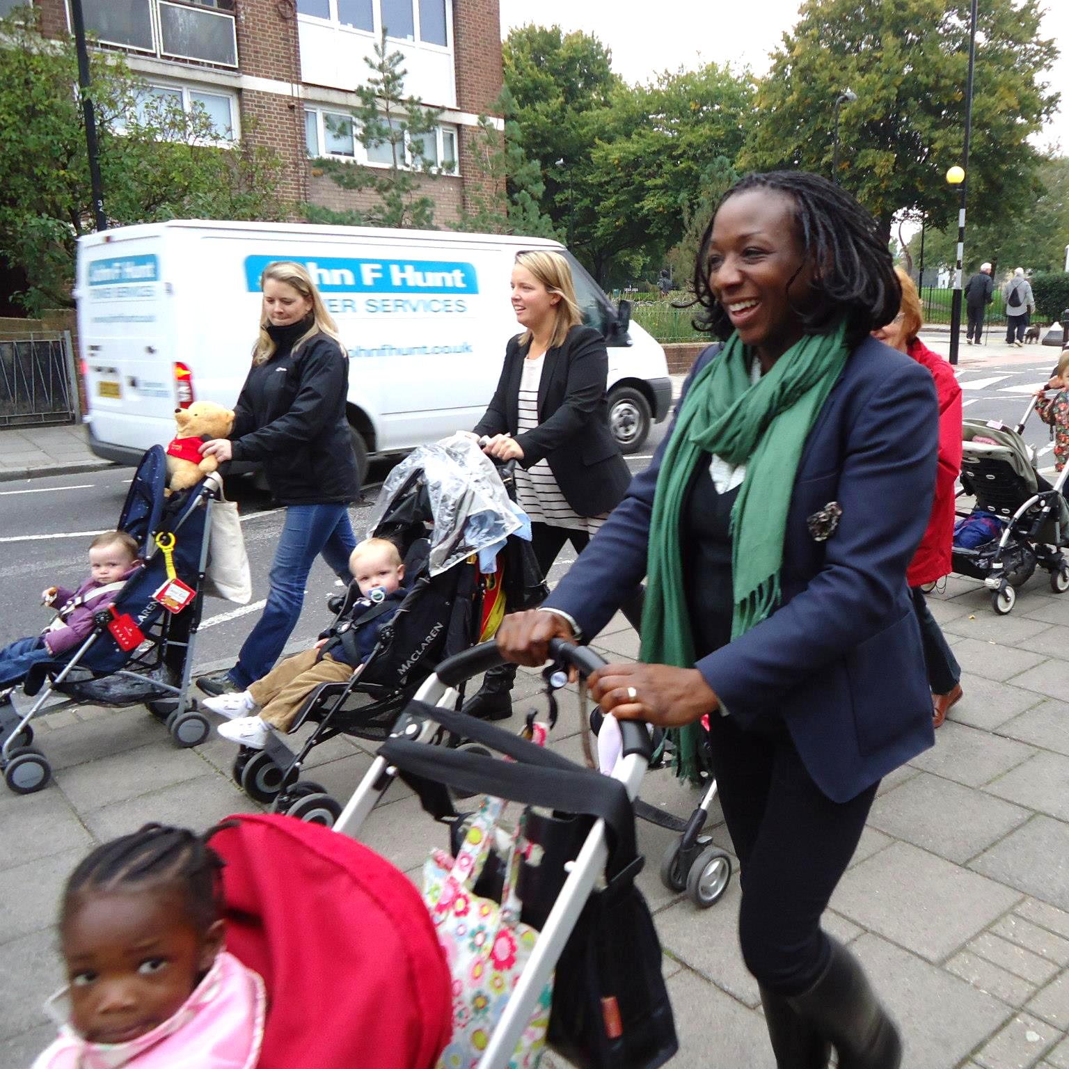 An action shot of several mums pushing buggies down the street on the way to a Firestation visit. They are smiling and laughing together.
