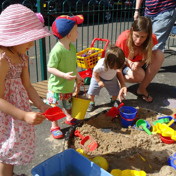 A mum and three small children play in a large tray of sand in a fenced off playground. They are using colourful buckets and spades to scoop the sand and make sandcastles.