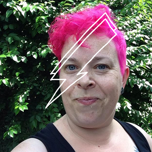 Head and shoulders shot of Claire. She has short pink hair adn stands in front of a leafy hedge. She is smiling stright into the camera in a quizzical way. She has a cartoon lightening strike down her face. She look very cool.