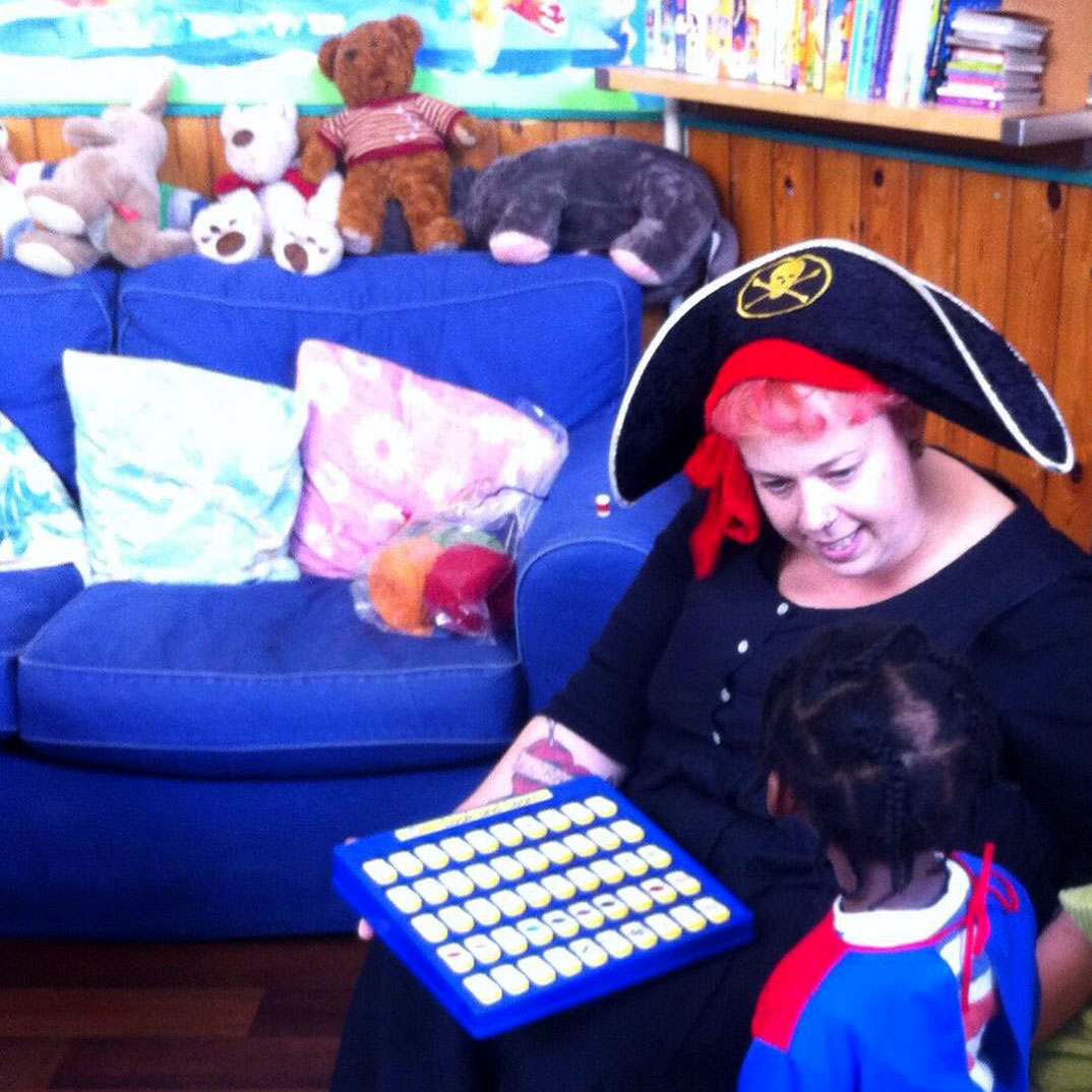 Centre Manager, Claire is dressed up as a pirate and playing a game with one of the children. They are sitting in front of our big blue comfy sofa. The sofa is covered in teddies.