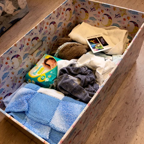 A large box covered in flowers filled with items for a new born baby. Nappies, vests, clothing and a blue hand knitted blanket. Part of our Growbaby offer.