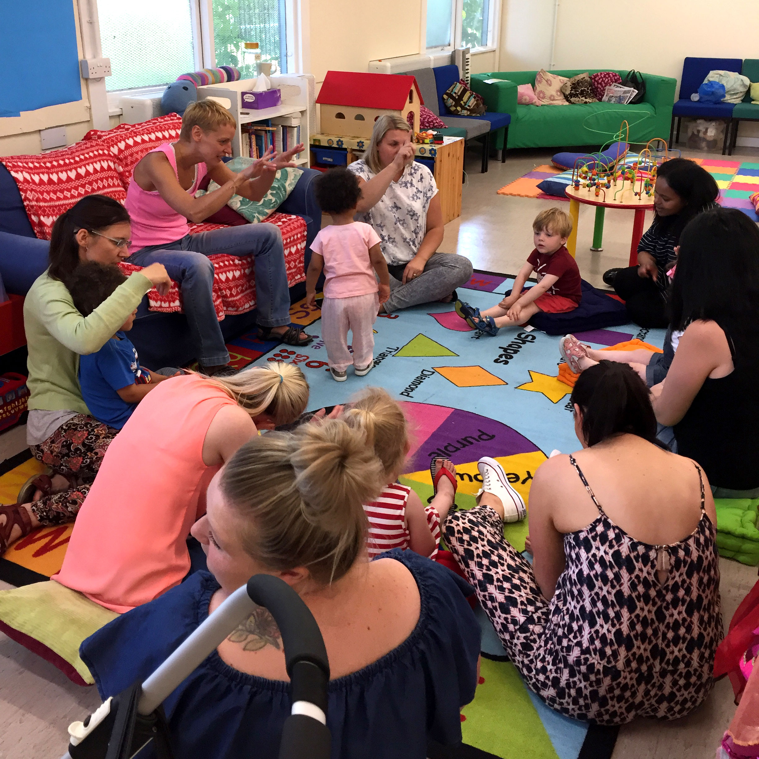 A group of Mums and babies sit on the floor in a circle for storytime. They are sitting on colourful ruggs with toys all around. Chloe is reading a story to them.