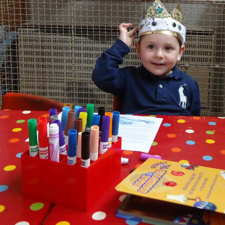 A little boy sits at a red spotted table with a cardboard crown on his head. He is smiling and touching the crown. On the table there is colouring pens and paper.