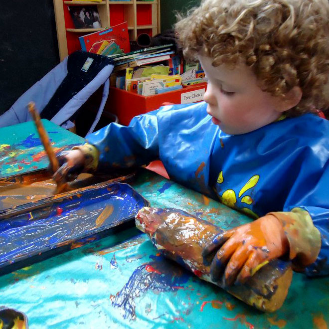 A little boy with brown curly hair sits at a table. He has a blue painting apron on and using a paintbrush to put blue and orange paint onto a bottle which he holds with his left hand. He is concentrating very hard and has paint all over his hand and the table.