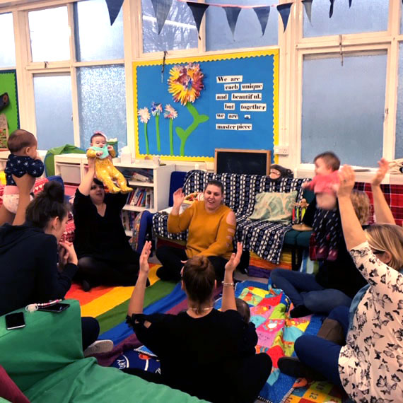A group of parents and children sit around in a brightly coloured room, they all raise their hands in the air.