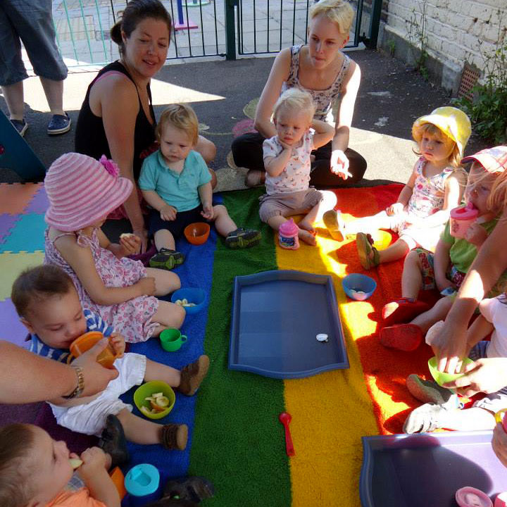 A group of children and mothers sit around a rainbow striped blanket eating snacks outdoors in the shade of a gazebo, sunlight streams down amongst them.