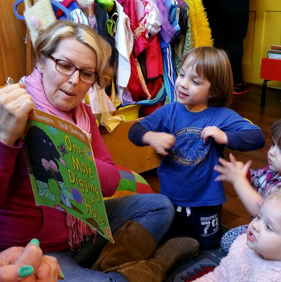 Angela sits on the floor reading a story book to some young children.She is looking at the book and pointing to the pictures, a young boy in a blue top is sitting in front of her and gesturing along to the story, he looks very animated and involved. There is a rack of dressing up clothes behind them.