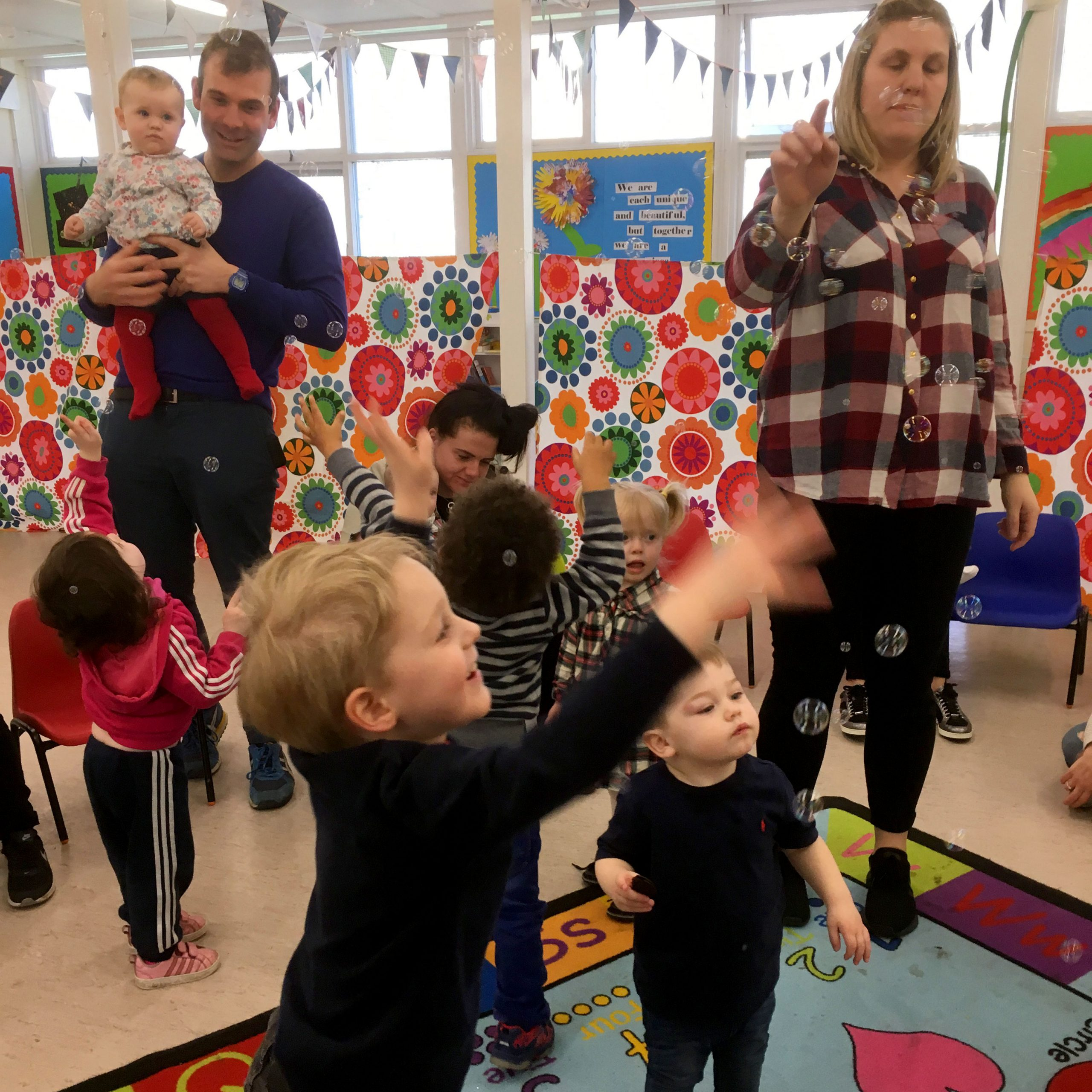 Adults and children dance around a colourful room catching bubbles. The children reach up in the air and a Dad is holding a baby to see the fun.