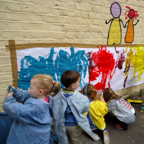 Four toddlers dressed in plastic painting aprons are painting on a large strip of paper taped to an outside wall. They have made big splodges of red, blue and yellow along the paper.