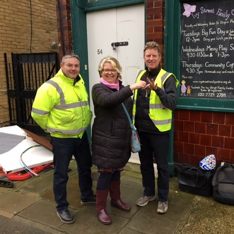 Angela stands between two of the builders in Hi-vis jackets. They stand in front of the door of Ivy Street and Angela is handing over the keys to the building. She has a big smile on her face.