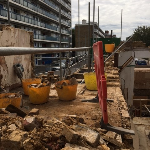 A view along the first floor as it is demolished brick by brick. Large plastic yellow buckets sit full of rubble and scaffolding provides safety around the edge of the site.