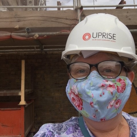 Angela on a site visit. She wears a white hard hat with Uprise written on it and a blue flowery mask, her eyes are smiling.