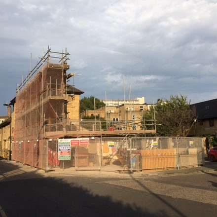 A wide shot of the building, the front wall is propped up with scaffolding, but the rest of the building has been demolished. The sun shines on the site which is surrounded by fencing to keep everything safe.
