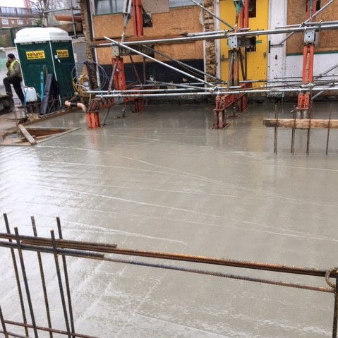A smooth concrete slab has been laid to cover the basement and will become the ground floor of the centre. The inside of the front wall is visible at the rear of the slab and steel reinforcement rods.