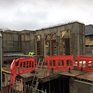 Walls and windows going up on the ground floor. Concrete walls with temporary wooden window frames around the grown floor space. The basement space can be seen in the foreground. Red safety barriers have been placed around the hole down to the basement. Lots of metal rods and concrete, but the progress is there.
