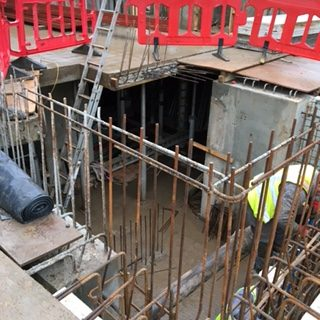 A view down into the basement space, the insulation to keep the basement warm and dry can be seen behind the concrete walls. The metal rod framework for the remaining walls is taking shape in the foreground. A ladder leans up against the ground floor to allow access down. A workman in a hi vis jacket can be seen working to secure the metal work..