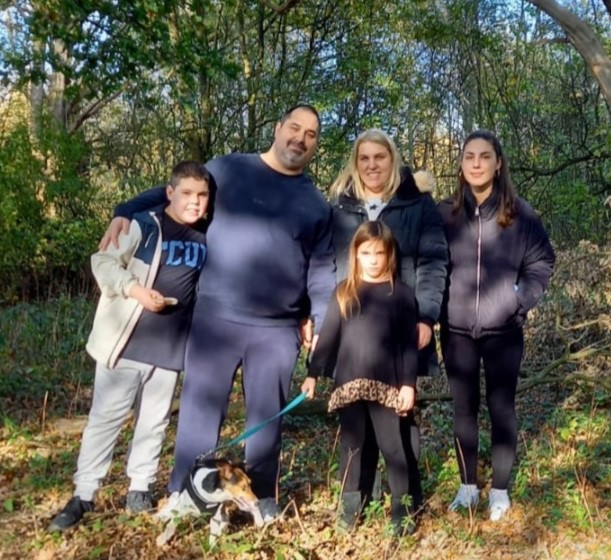 Chloe and her husband with their three children and their Jack Russel terrier, all dressed in dark blue. stand in a group in the dappled light of surrounding trees.