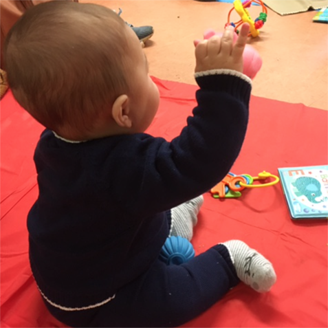 A small baby sits on a red mat and plays with some small plastic toys. He holds a rattle up with his right hand.