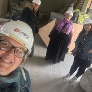 The team stand socially distanced in the building site of the new building. Angela is taking the selfie and everyone is wearing hard hats with the word Uprise on them. Uprise are the contractors doing the build.