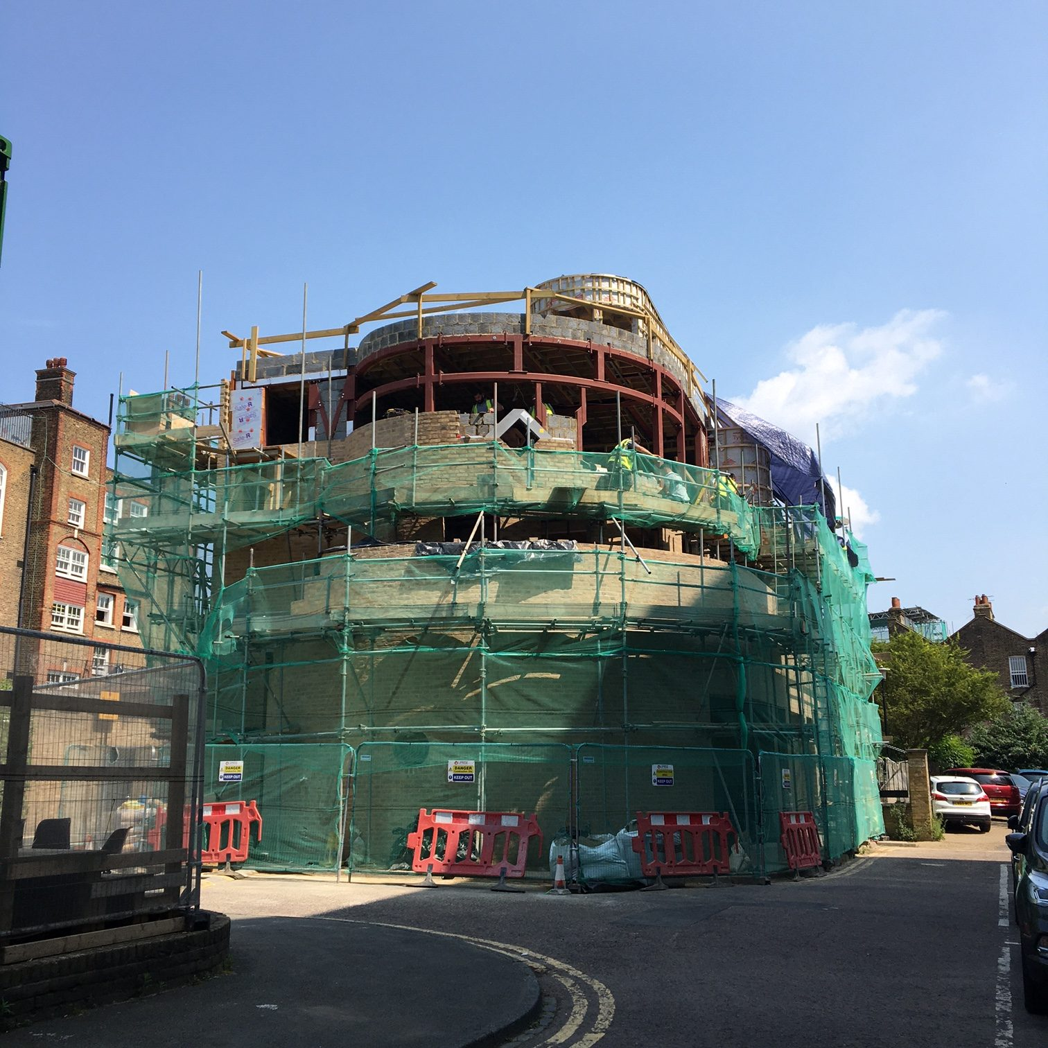 A view of the west side of the building with brickwork up to the second floor, with some windows in place. The red steel structure can still be seen on the third floor. A small curved room can be seen right a tthe top. The whole building is surrounded by scaffolding and green mesh. It's starting to look very impressive.