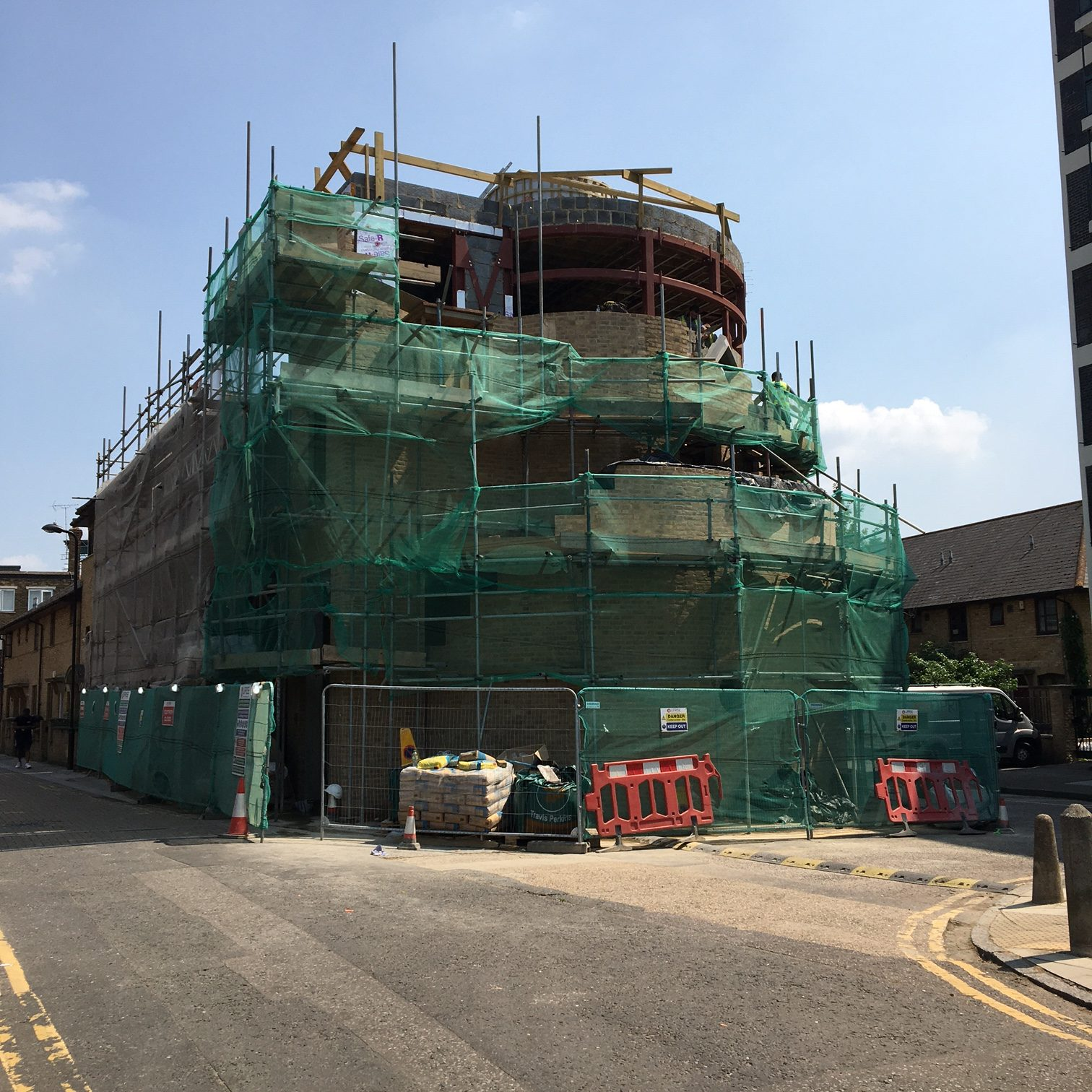 View of the building from the west along Ivy Street. The lowere floors are covered in bricks and the steel structure is still seen on the upper floors. Scaffolding  adn green mesh surround the  building. The old pub front is still visible behind the front scaffolding.
