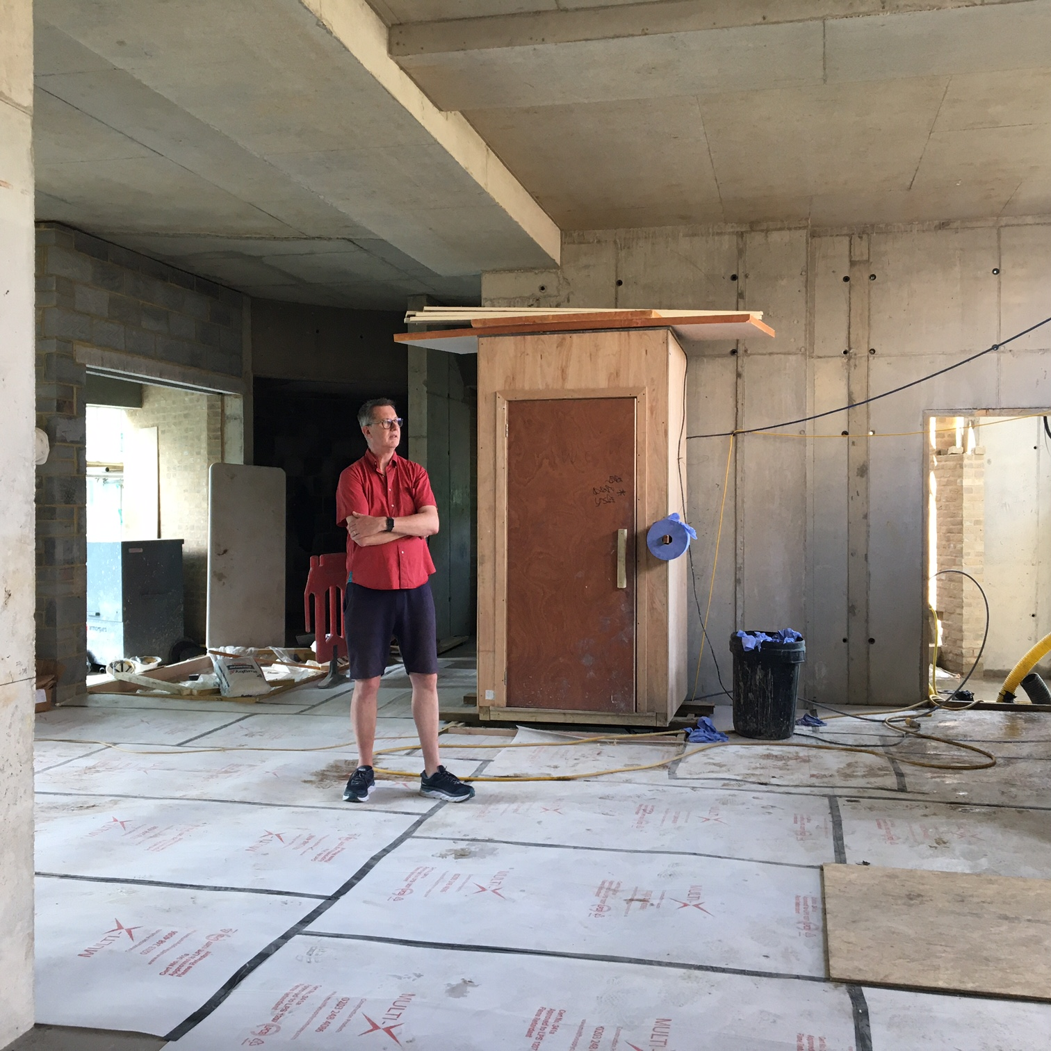 Andrew who is almost 2 metres tall stands in the main space of the building. The ceiling is far above his head and there is lots of space around him. The walls are still concrete and the floor is covered in a protective plastic sheeting.
