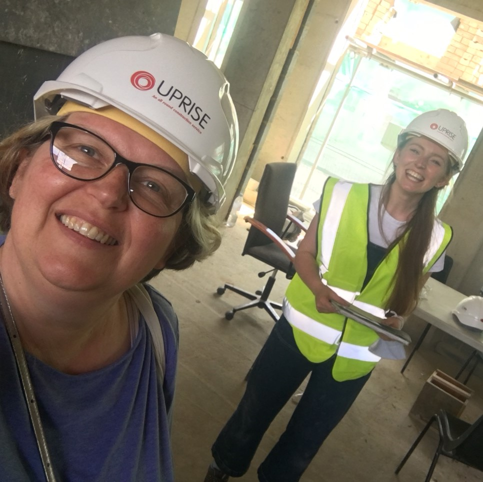 Selfie with Angela close to the camera and Hannah from Sarah Wigglesworth Architects in the background. Both in hard hats and grinning widely. Inside the building with concrete floors, walls and ceiling and various builders materials lying around. Hannah is wearing a hi vis jacket and holding some drawings.