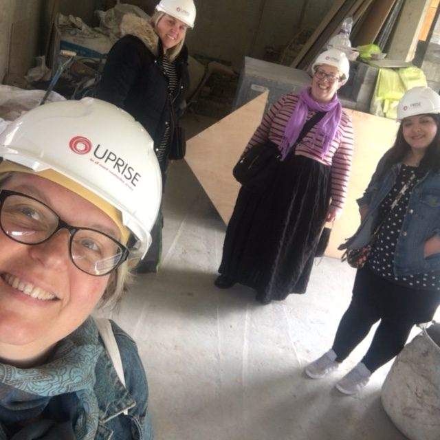Selfie taken by Angela with Claire, Chloe and Victoria behind her. They are all wearing hard hats. They are inside the building for the fist time. Concrete walls, ceiling and floors with lots of building materials lying around, but they all look very happy and excited to be inside at last.