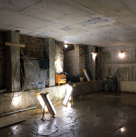 An empty basement room just concrete with temporary lights, you need to use your imagination to see the sensory play room that will be here.